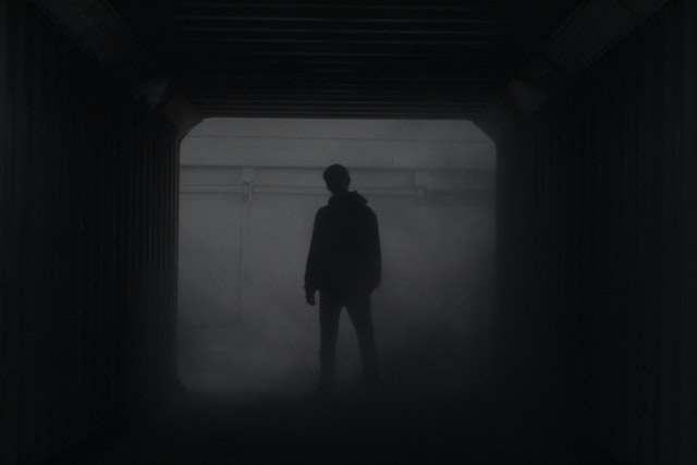 Fear: Silhouette of a man standing in front of dark window