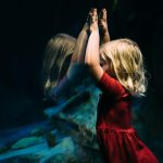 Inner critic: girl in red dress seeing her reflection in the mirror