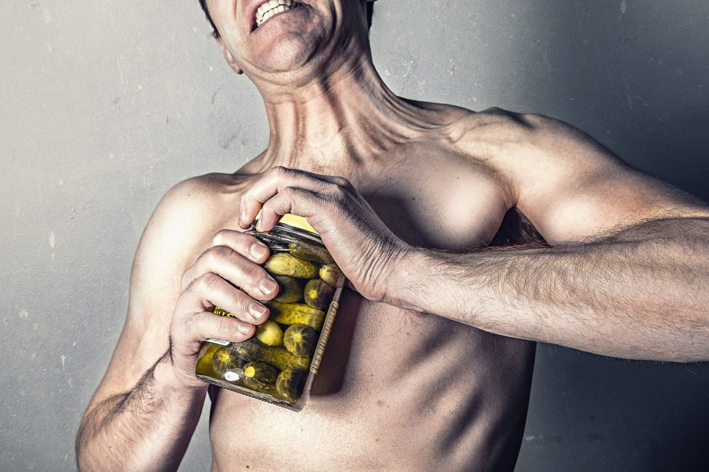 Man struggling to open a jar of pickles