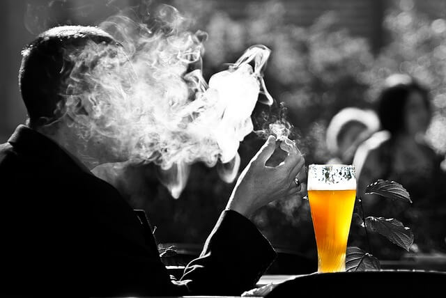 man smoking and drinking in a bar