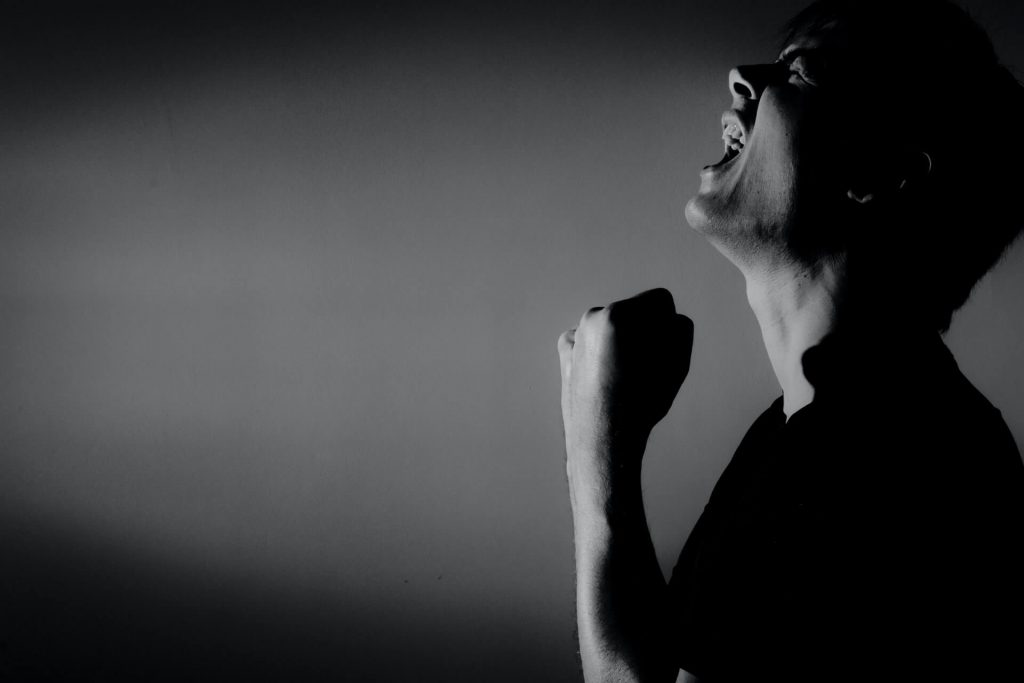 Black white photo of a man yelling because he repeated a same mistake