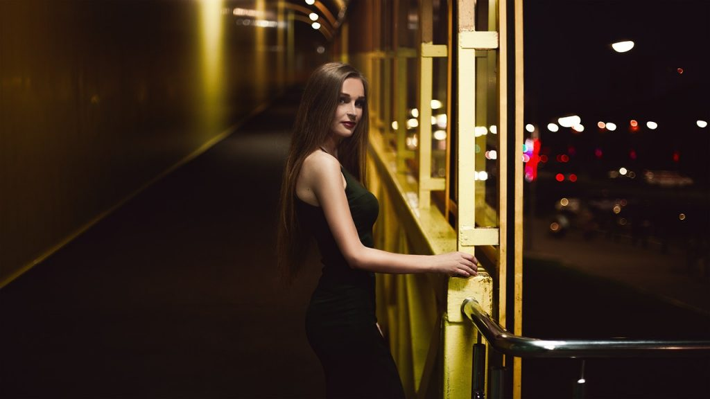 Pretty young girl in a black dress on a balcony