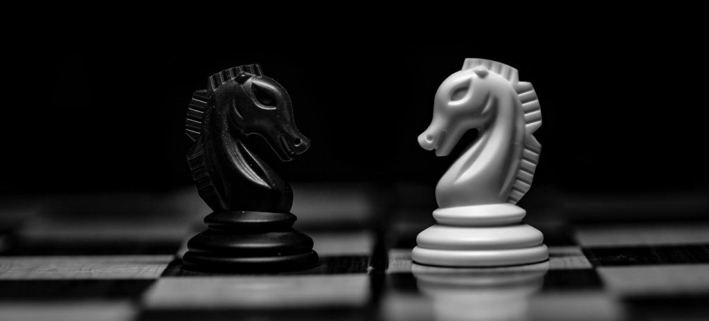 Batman vs Superman: black and white chess pieces on a dark background
