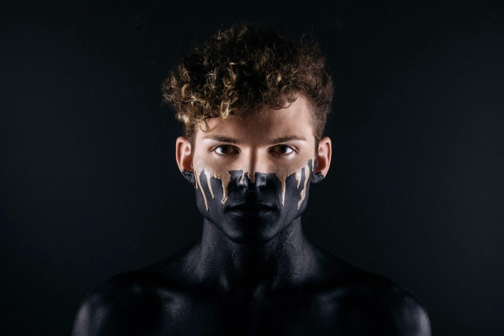 young man covered with black body paint on dark background