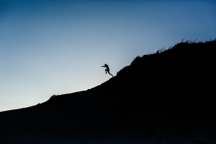 Man jumping from a silhouette of a mountain with blue horizon in the background